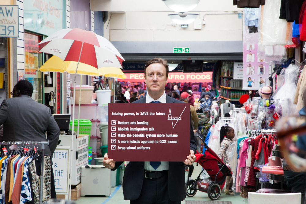 <p>Art Assassins' political manifesto held by David Cameron lookalike Bentley Browning, May 2015. Photo: Manuela Barczewski.</p>