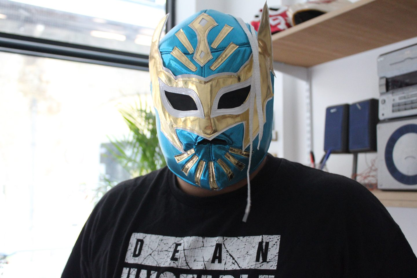 Art Assassin Mehmet Cucel poses with a wrestling mask during a visit to Andrea Franke's studio.