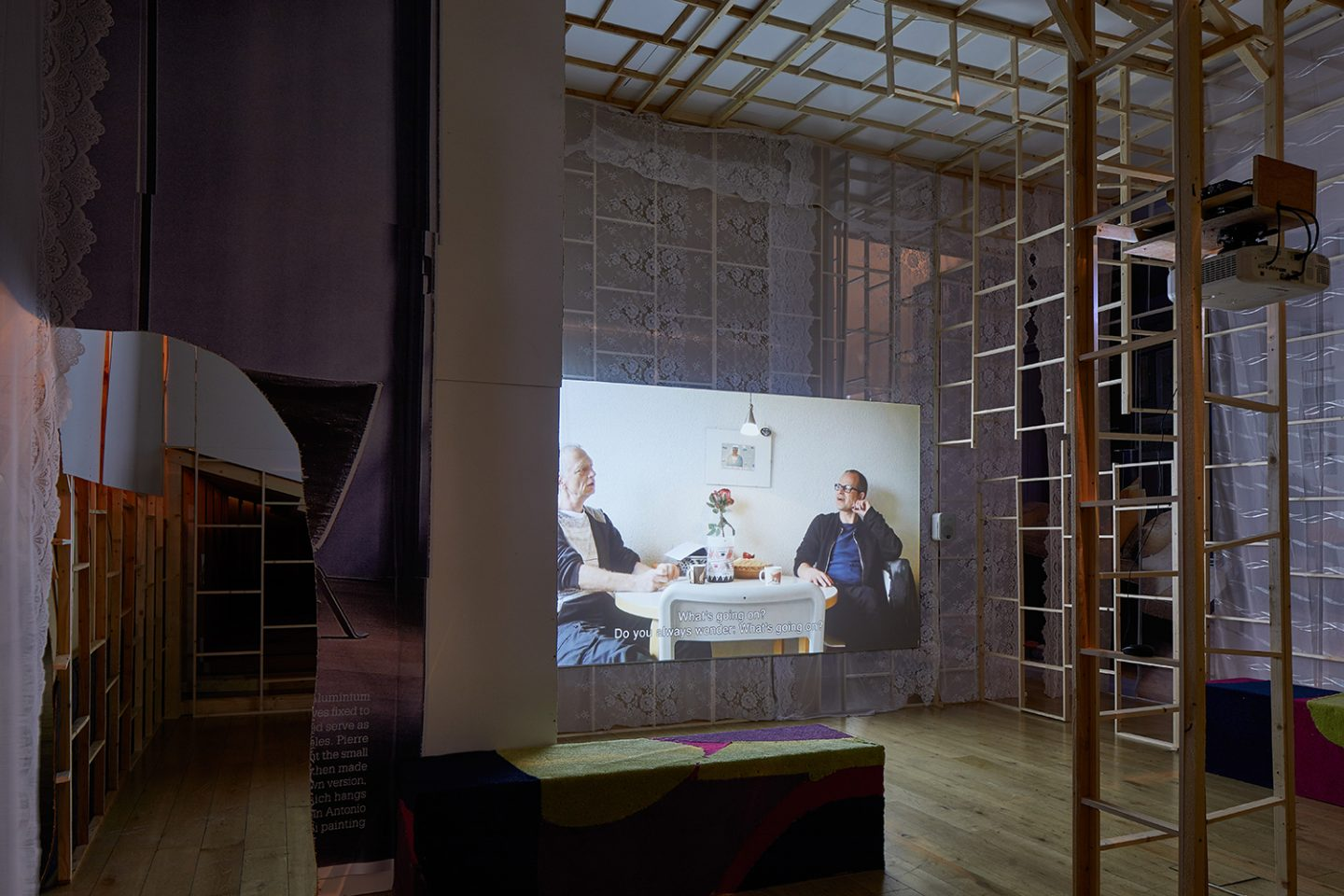 Erik van Lieshout, Janus, 2012. Exhibition view at the South London Gallery, 2017. HD film, colour, sound, 50 minutes. Wood, carpet, lace curtains. Courtesy the artist, Maureen Paley, London and Galerie Guido W. Baudach, Berlin; Annet Gelink Gallery, Amsterdam. Photo: Andy Stagg.