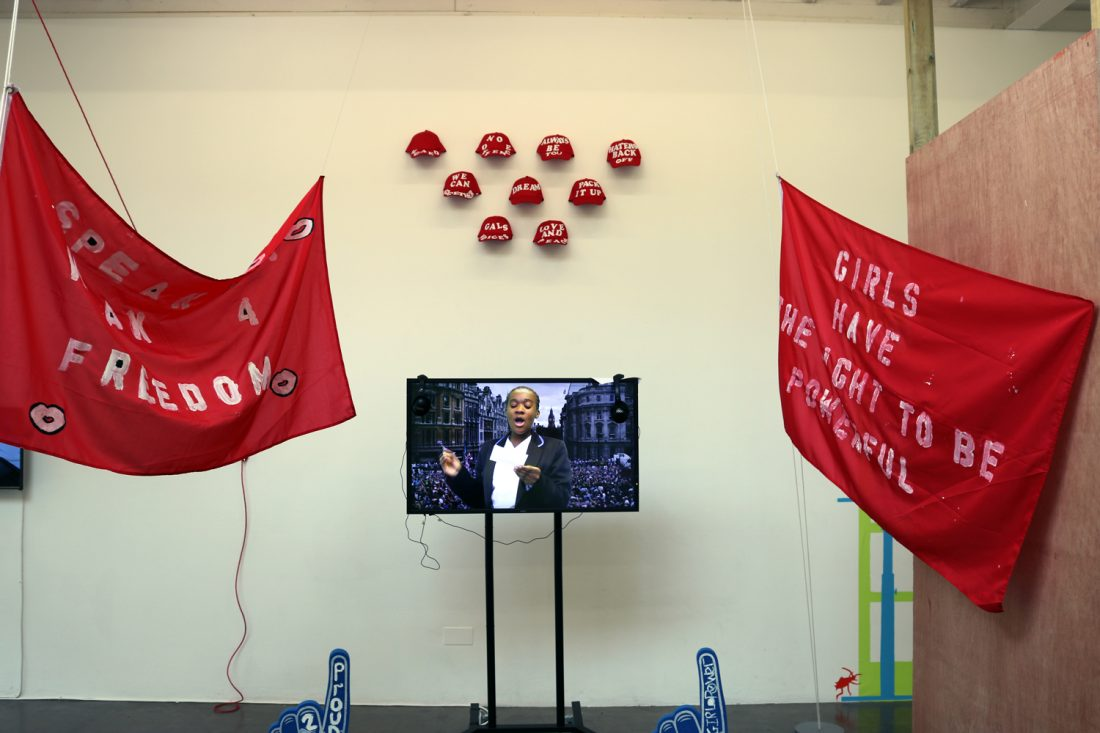 <p>Campaign video flanked by two red flags bearing slogans about women's and girls' rights as part of The Schools' Exhibition: Jack Petchey Start Programme in the Clore Studio, 2017</p>
