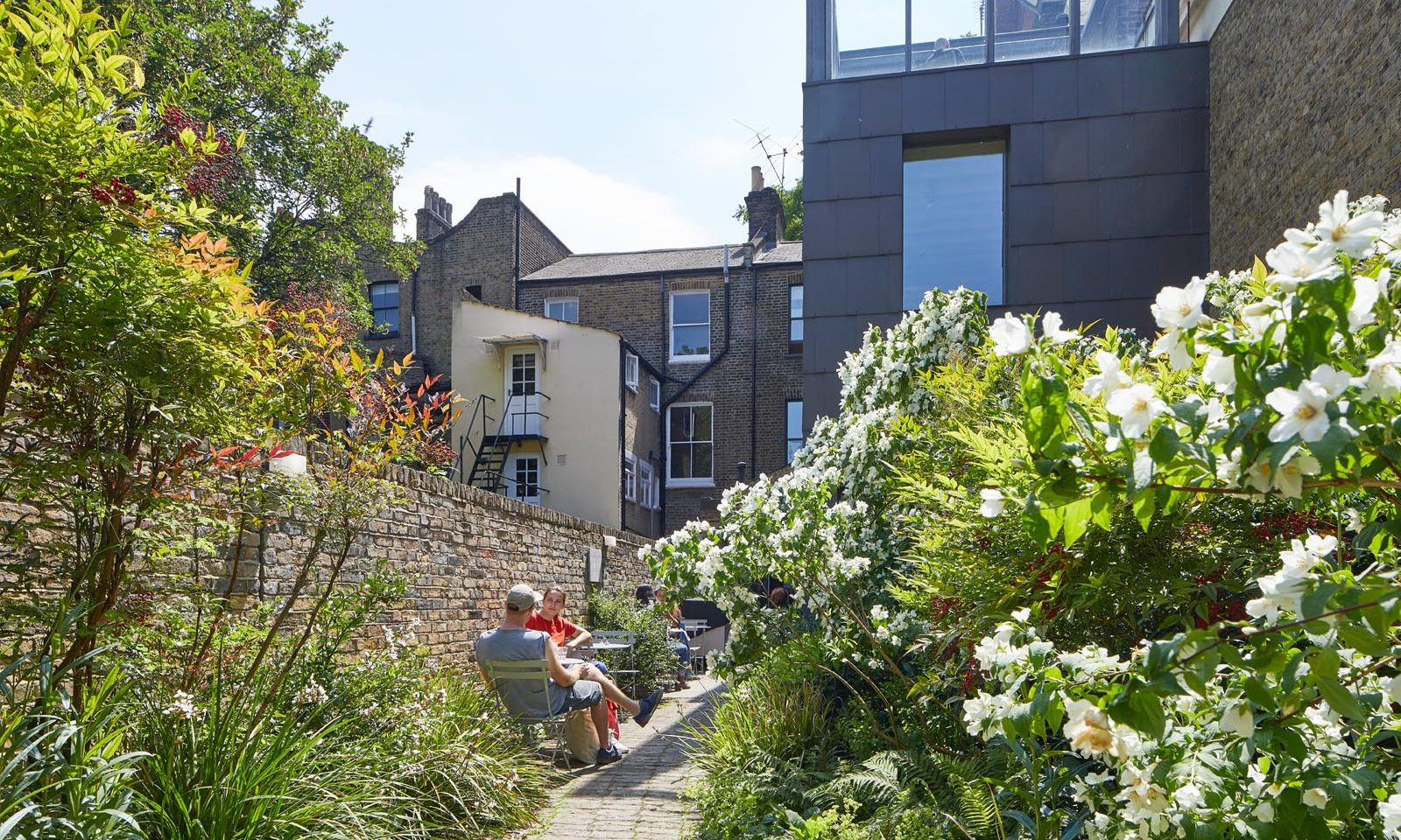 This photo is a view of the SLG's Fox Garden, it shows bushes and plants in the foreground, a person sitting on a chair in the mid-ground and the building of the gallery in the background.