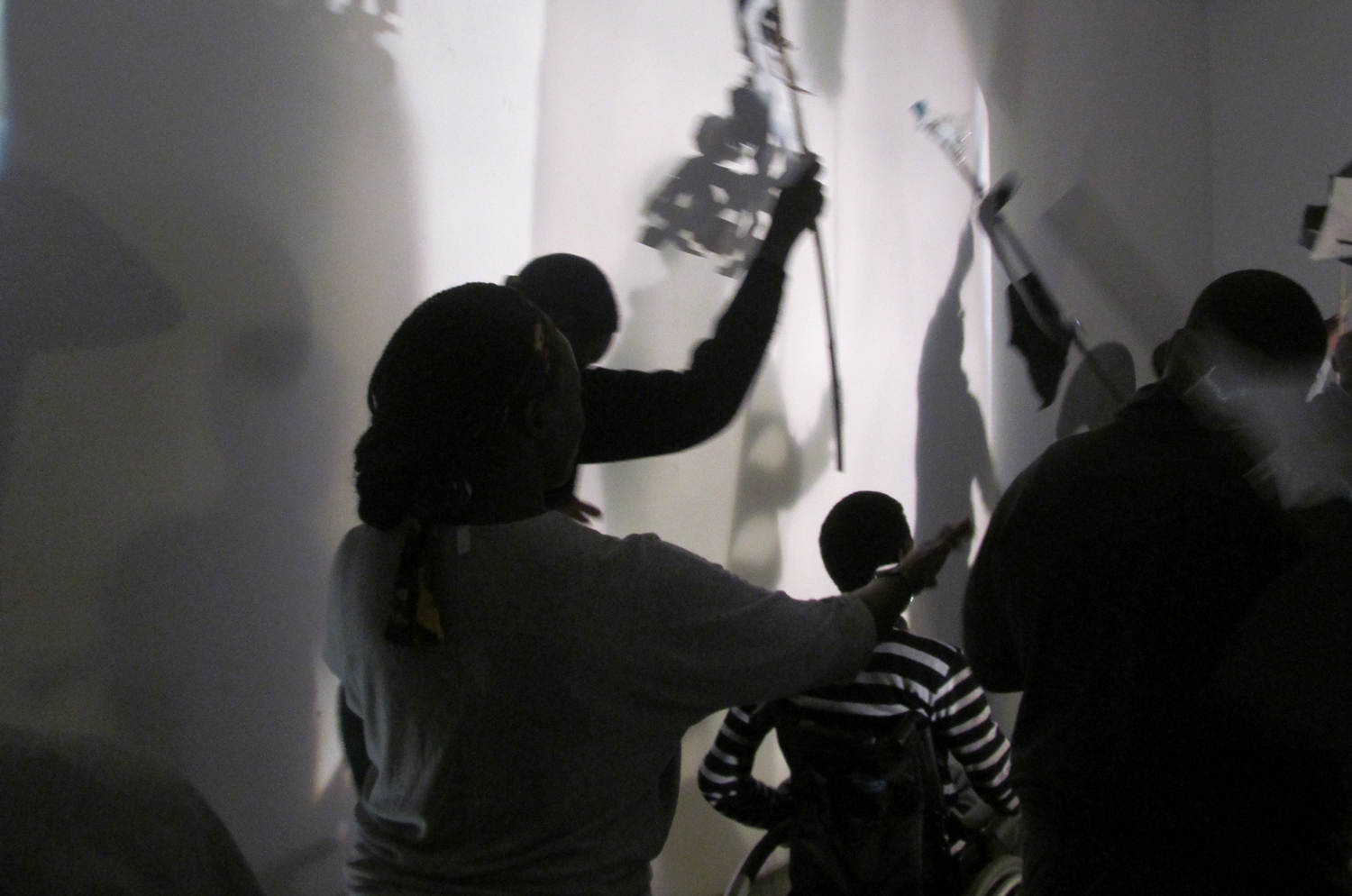 This is a black and white image of several figures including a wheelchair-user facing away from the camera towards a brightly lit wall. The group are creating artful shadows on the wall with paper creations on sticks.