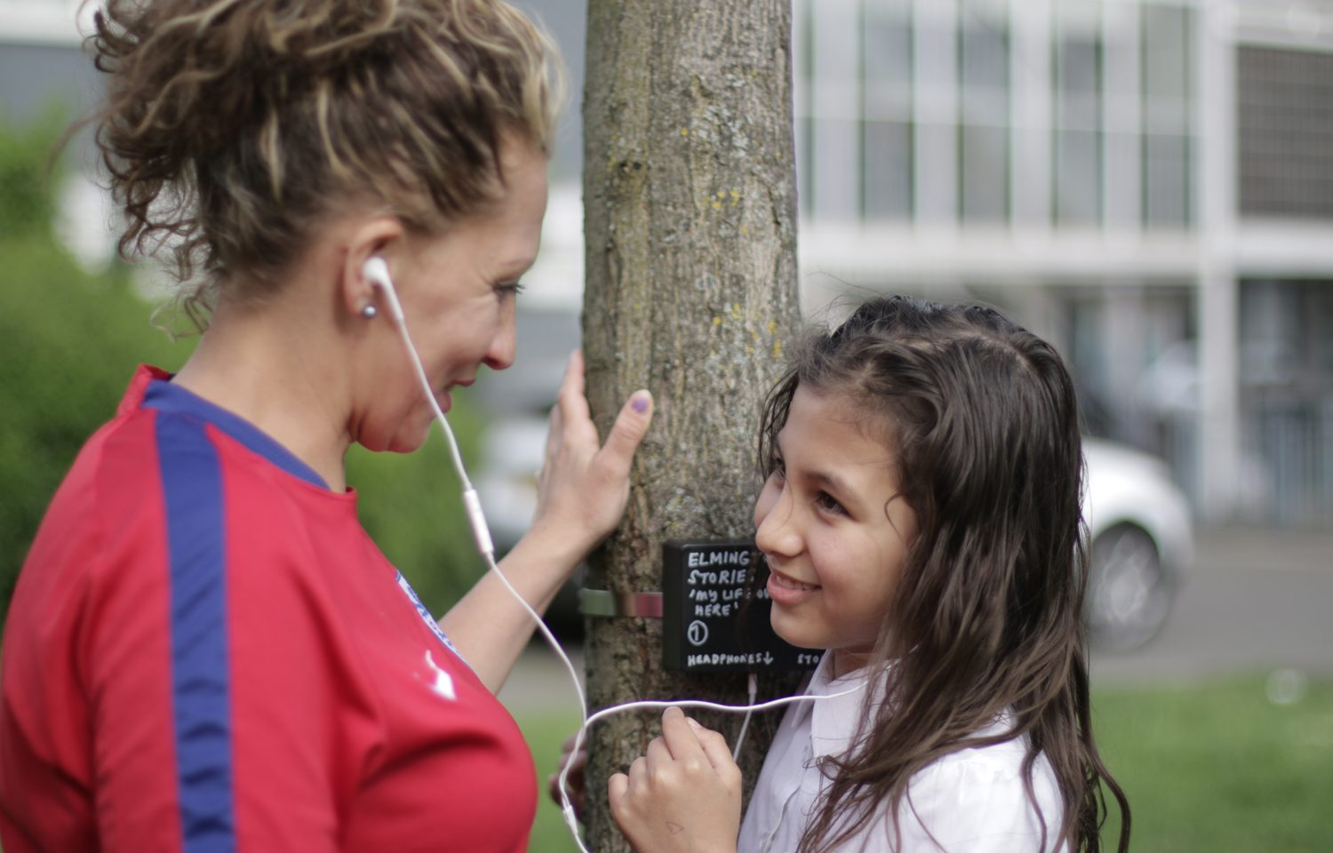 A woman and a girl are looking at each other and smiling. They are each listening to one headphone, and both are touching a tree in the middle of them.