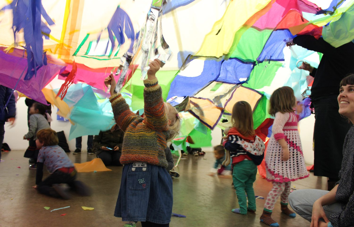A small child raises her hands to the air to touch lots of pieces of coloured tissue paper above her. Behind other children are playing. To the right of the picture going out of the shot a woman is crouching down and smiling.