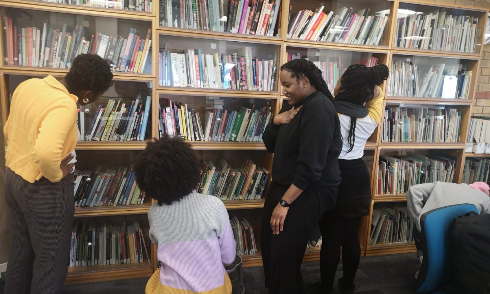 Four people stood in a library looking at the book shelves