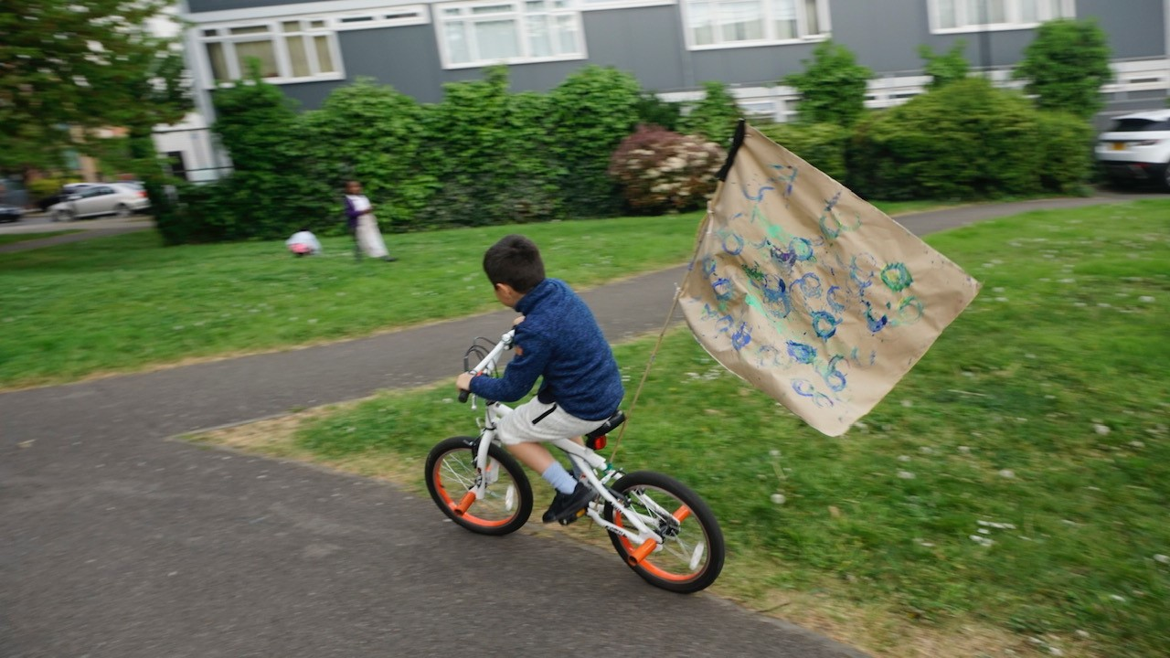 Child riding bike with flag attached to the back
