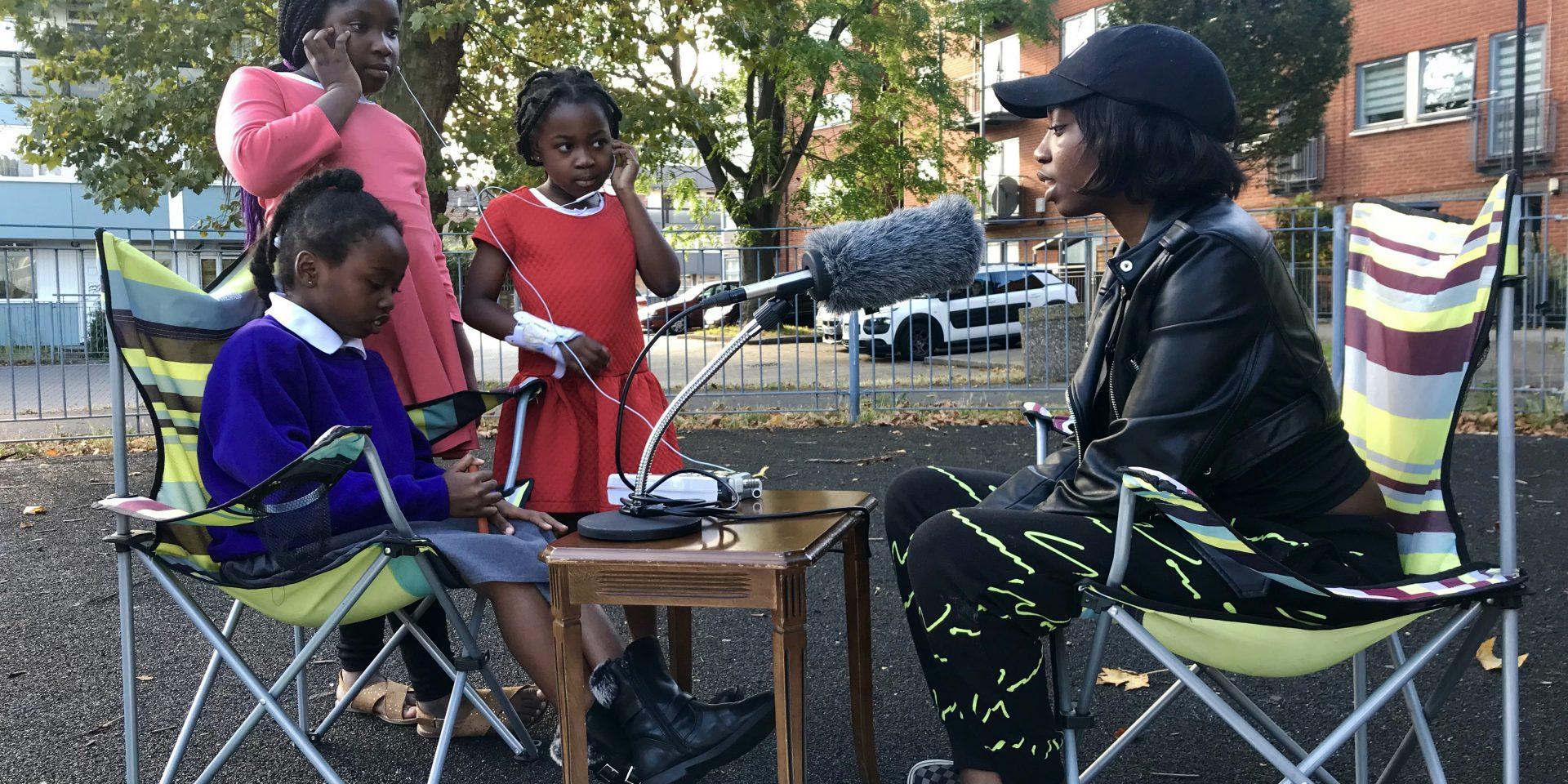 Three children interview an adult sat outside