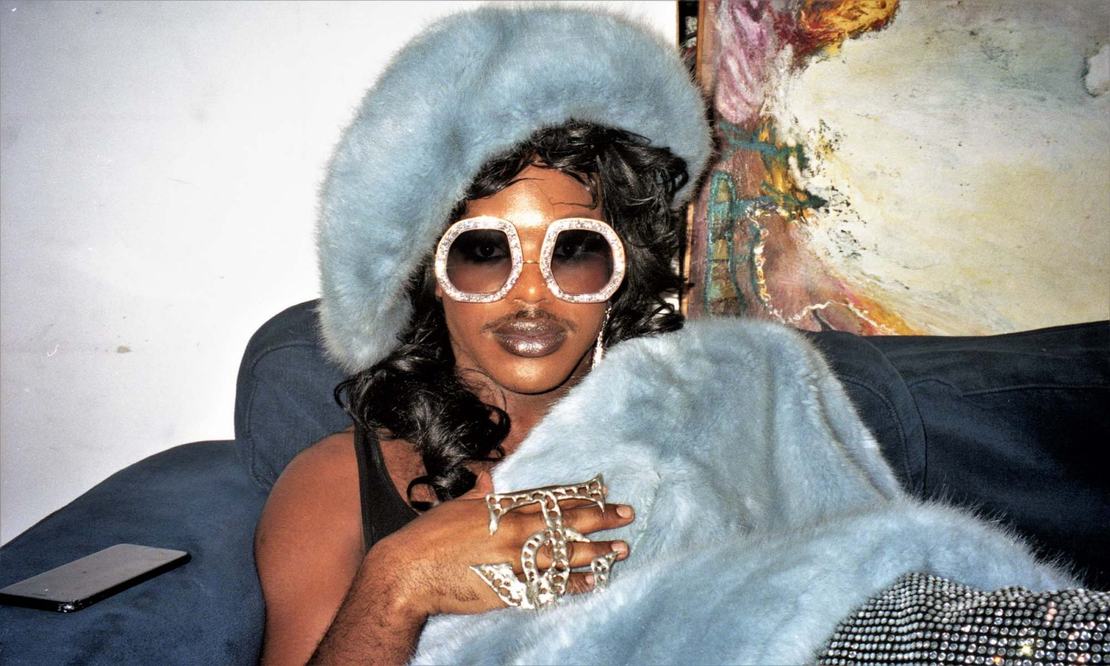 Miss Jason wears blue fur hat and large white sunglasses, looks at camera