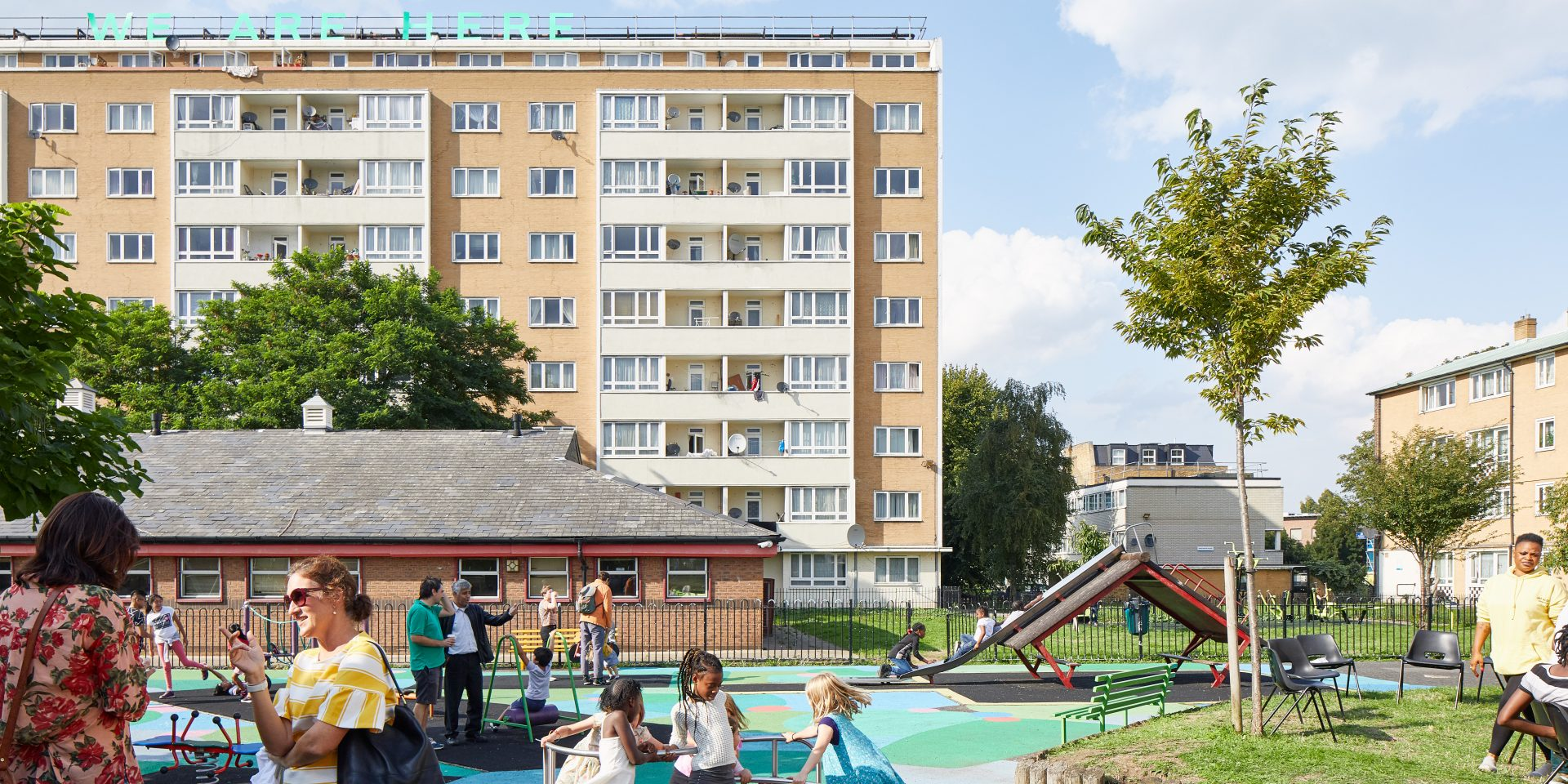 Text work 'WE ARE HERE' on top of block of flats; children playing in playground, with brightly painted surface