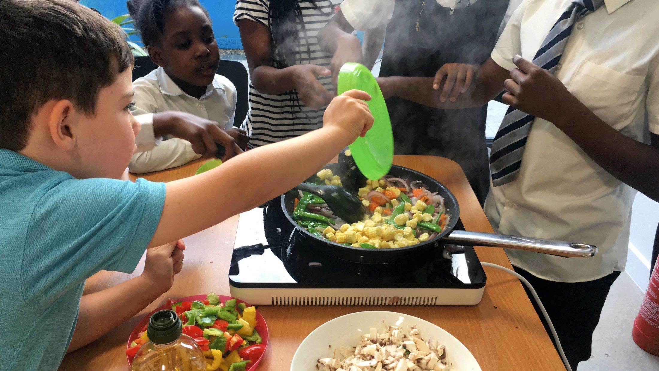 Children put vegetables into a frying pan to cook stir fry
