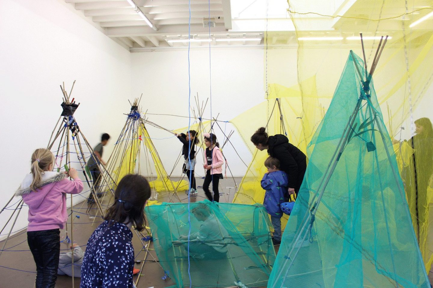 Children build tent like structures in a Sunday Spot workshop