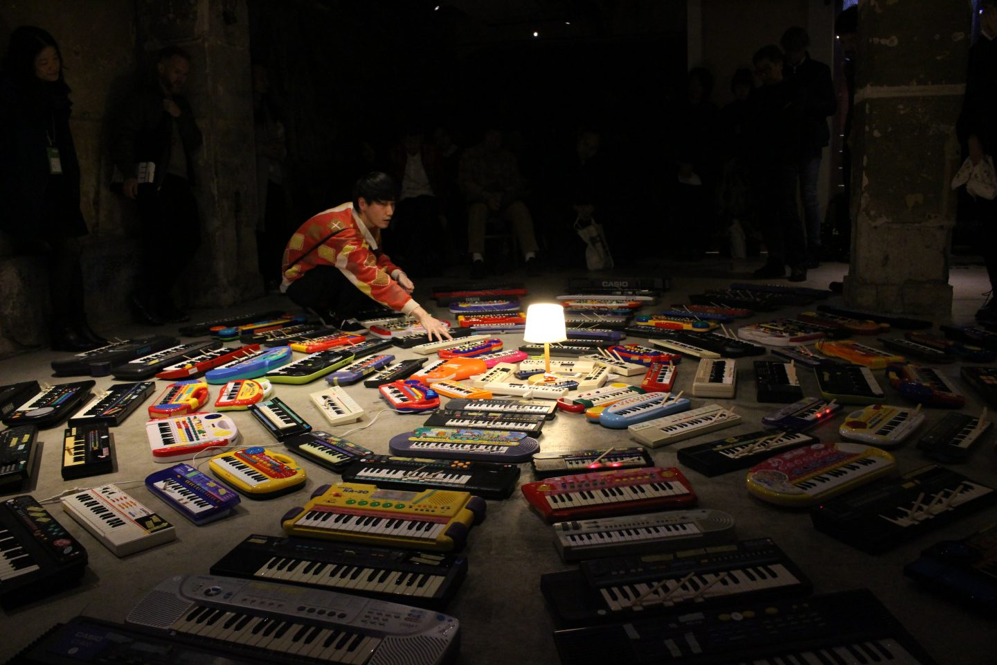 The artist sits at the edge of concentric circle of keyboards placed on the floor