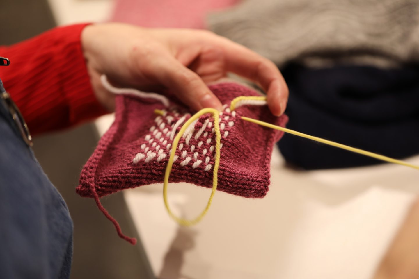 A hand holds fabrics whilst stitching it