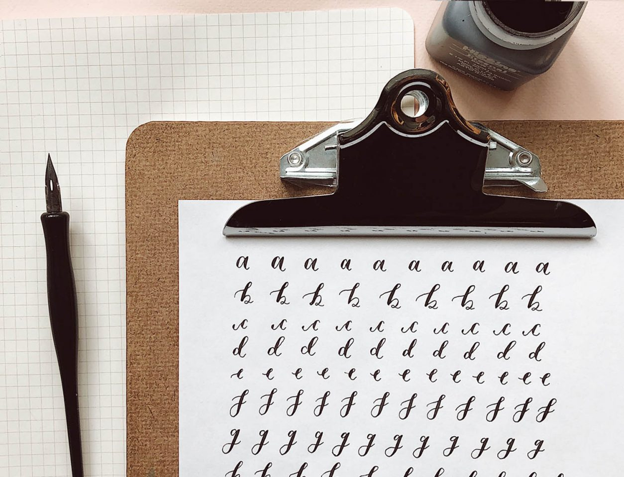 A clipboard with a hand-alphabet on paper written in ink