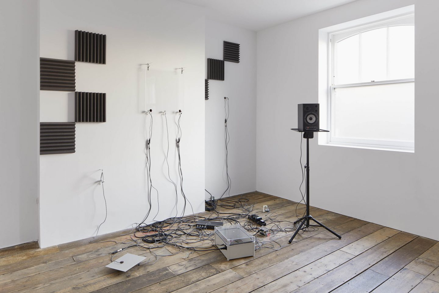 A tangle of wires on the floor linked to a free standing speaker and speakers wall mounted