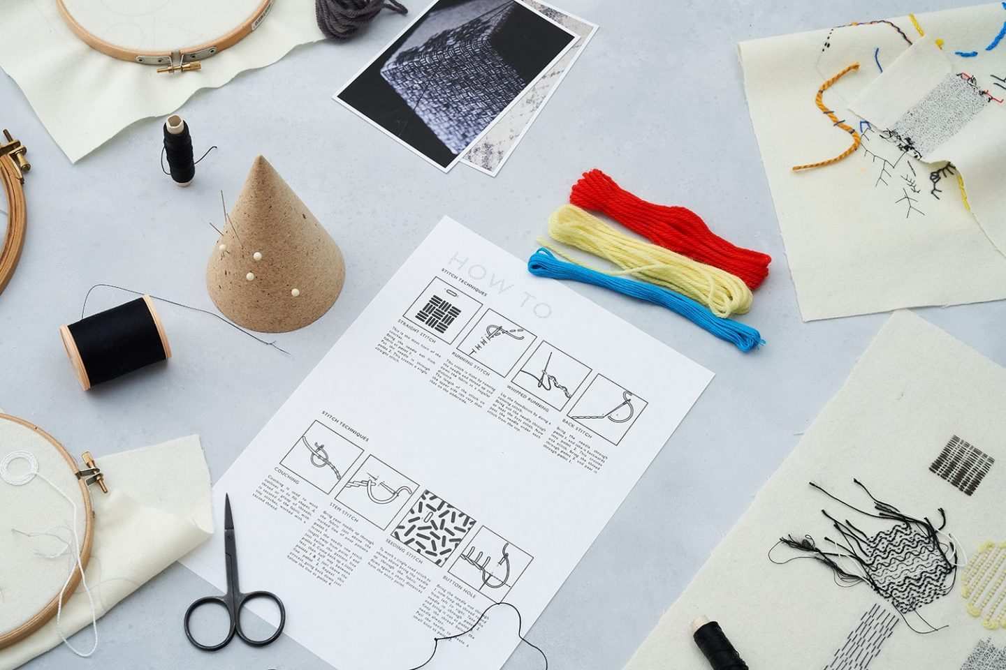 Photograph shows bundles of thread, an instruction sheet, scissors and material with some hand embroidered patterns