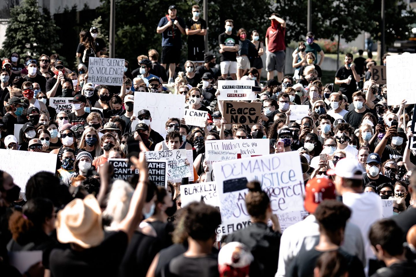 A crowd of protesters wearing masks and holding placards protest against police brutality and racism in the US