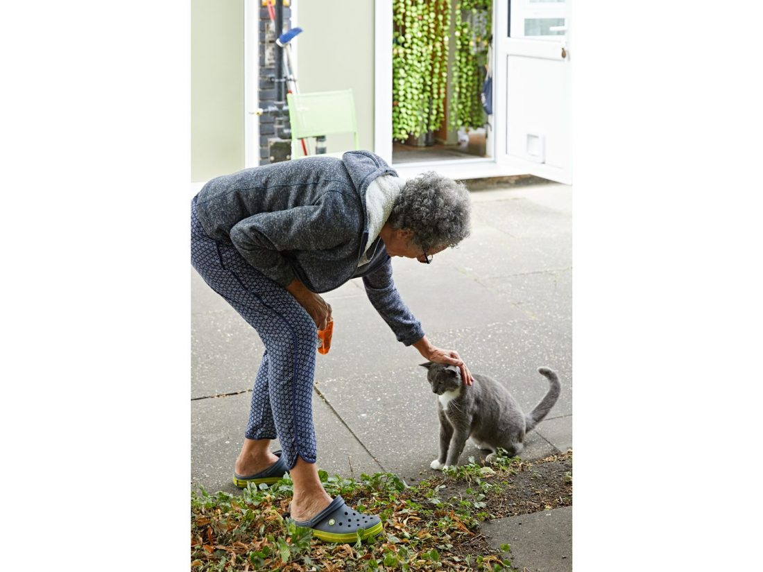 <p>Liz in the Sceaux Gardens community garden with Albert the cat. Photo: Andy Stagg</p>