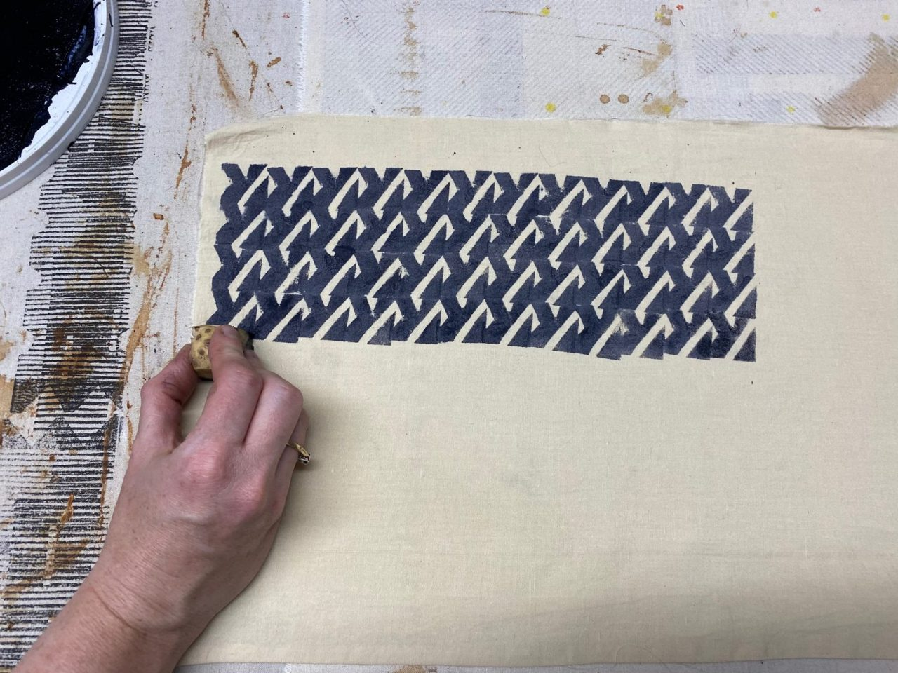 A hand using a block to create a print on fabric
