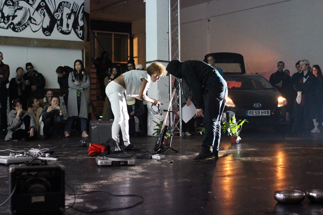 Two people stand in the centre of a room, one person is holding recording equipment and there is a speaker, turntable and houseplants on the floor. An audience watches them from the side-lines