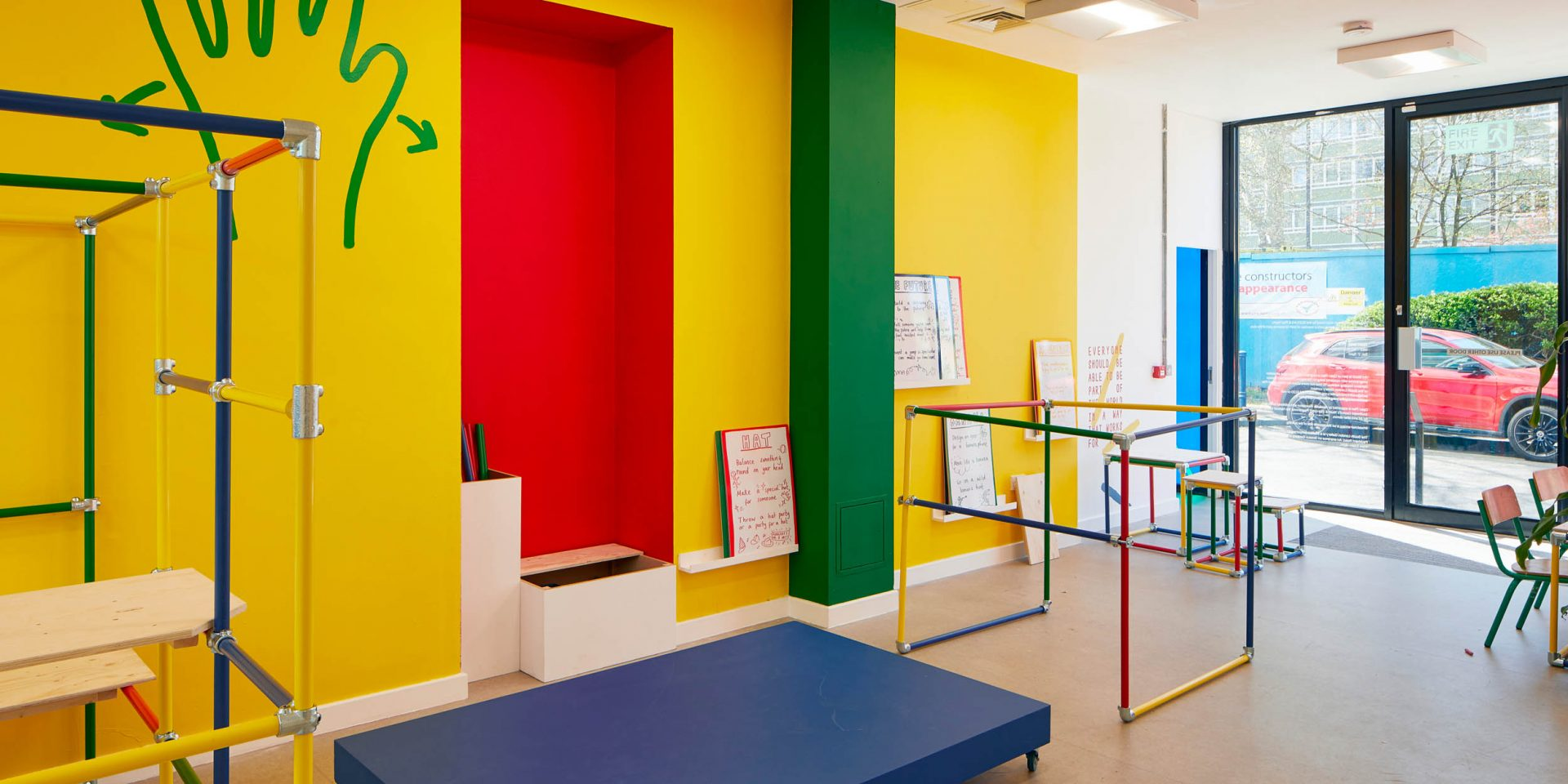 Art Block with a brightly coloured yellow wall, a brightly coloured wood modular structure and a green hand painted onto the wall
