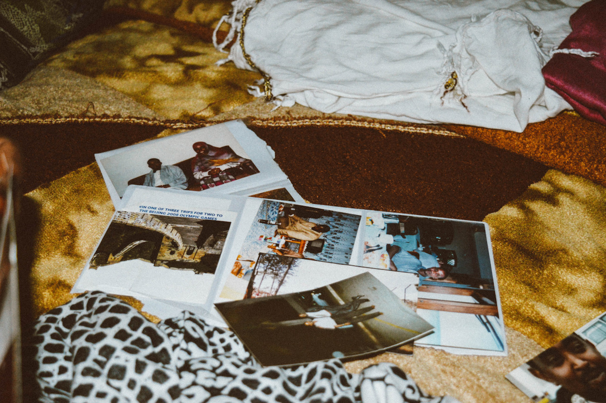A selection of family photographs overlap on a bed