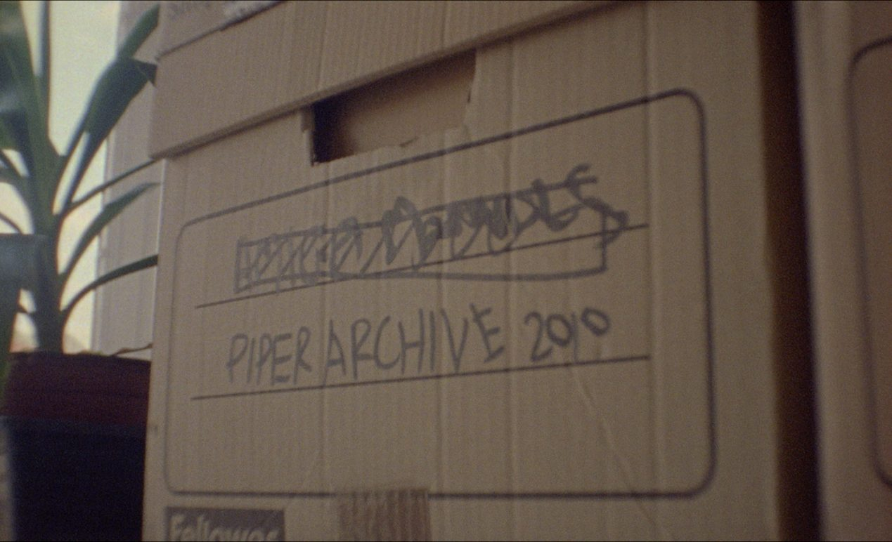 A brown cardboard box with 'Piper Archive 2010' scribbled on