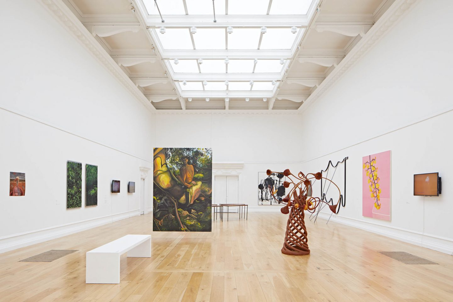 The SLG's Main Gallery with paintings on the wall, a sculpture with a conical shape and tree like limbs protruding out, and a painting hangs from the ceiling in the middle of the room