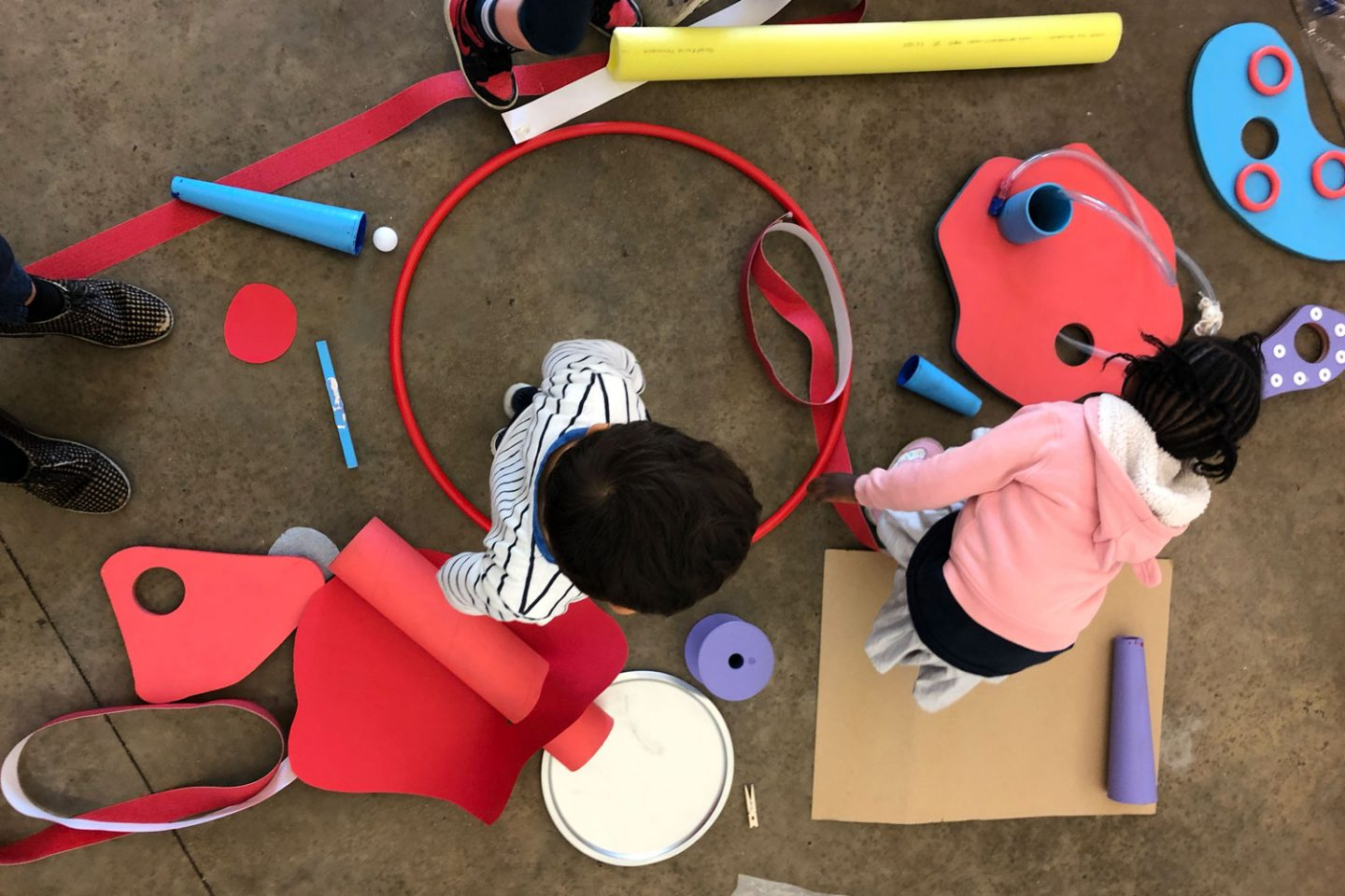 Two children surrounded by colourful paper, a hula hoop, card, and tape