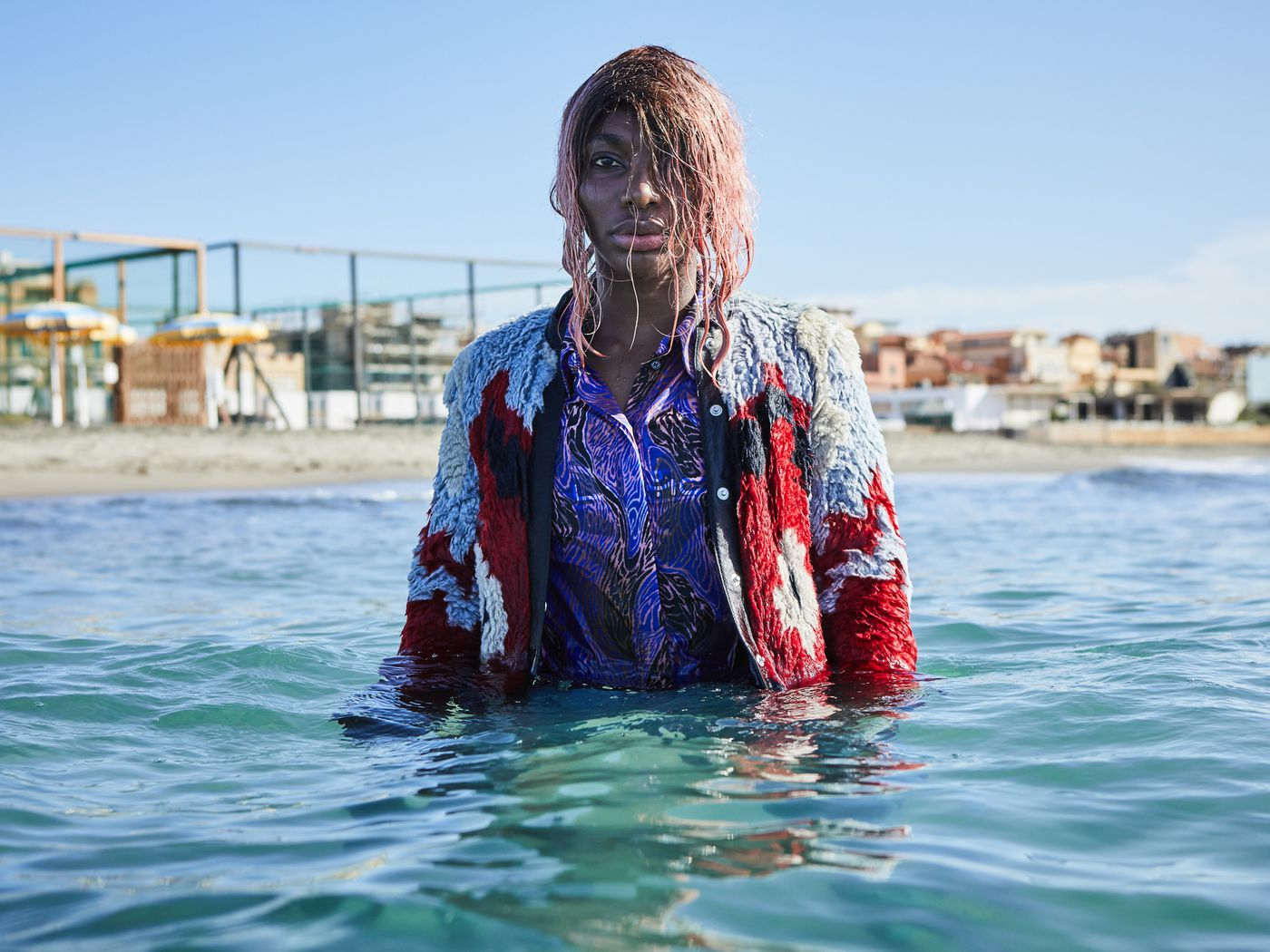 Michaela Coel stands in the sea with pink hair