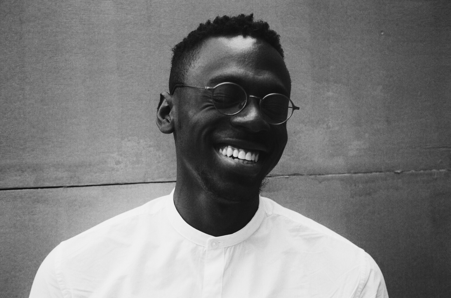 Black and white photo of Axel Kacoutié who wears glasses and is smiling with his eyes closed